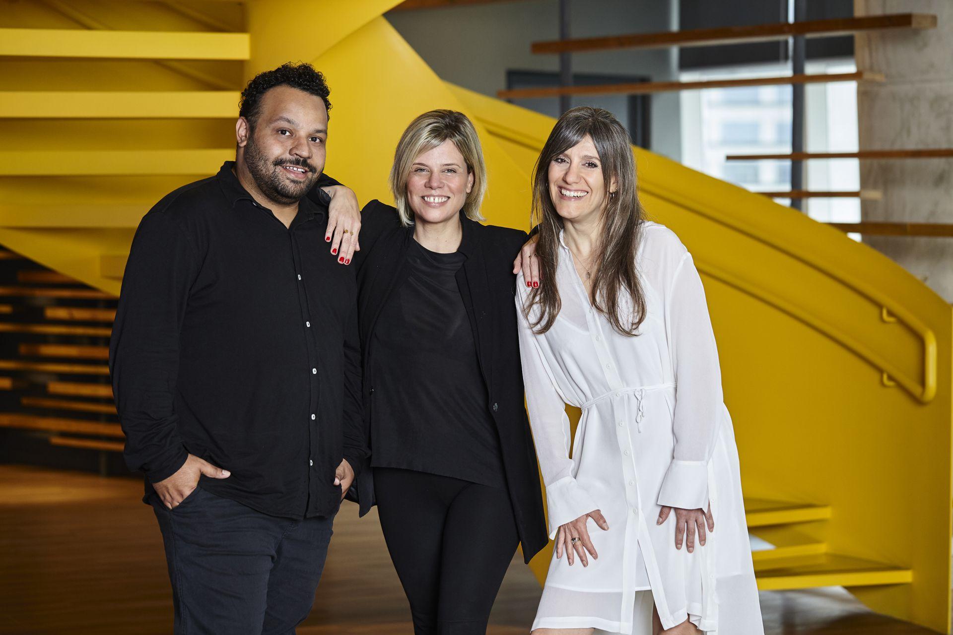 Três colaboradores da agência em foto do time, um homem e duas mulheres à direita. São eles: Maurilio Filho, Renata Bokel e Marie Alonso