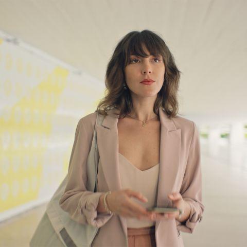Uma mulher elegante caminha por um corredor olhando em frente com determinação. A parede da esquerda possui curvas amarelas. A mulher veste blêizer na cor bege, segura uma bolsa embaixo do braço esquerdo e segura um celular com as duas mãos.
