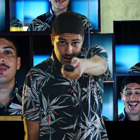 Um jovem aponta um controle remoto para frente. Atrás dele há um mosaico de televisões ligadas mostrando o rosto do rapaz com diferentes expressões faciais.
