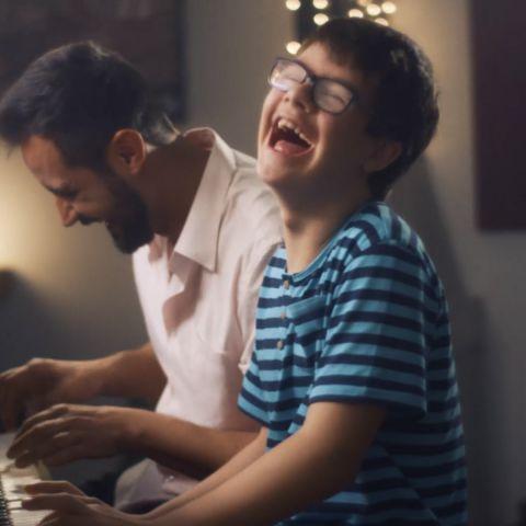 Um menino sorri enquanto toca piano ao lado do seu pai