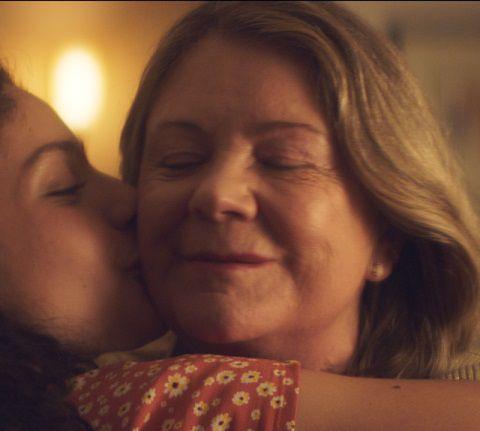 Garota beijando sua avó no rosto durante ceia de Natal
