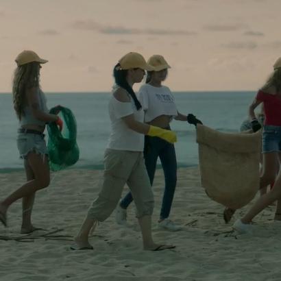 Grupo de pessoas andando na areia da praia, recolhendo lixo