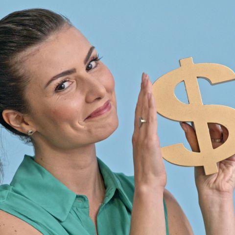 Foto da especialista em finanças, Nathalia Arcuri, sorrindo e segurando um cifrão.