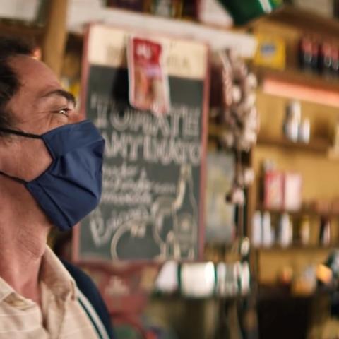 Na imagem, a cena de um comerciante, atrás do balcão de sua loja, usando máscara de proteção e com uma expressão de sorriso.
